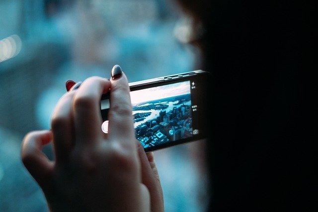 Detail rukou držících mobil, pořizujících fotografii